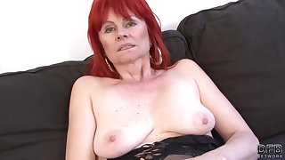 Red-hot haired granny in erotic lingerie is having lucky sex around a black guy, on the sofa